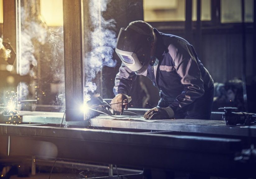 Welder with protective equipment welding metal in small workshop.